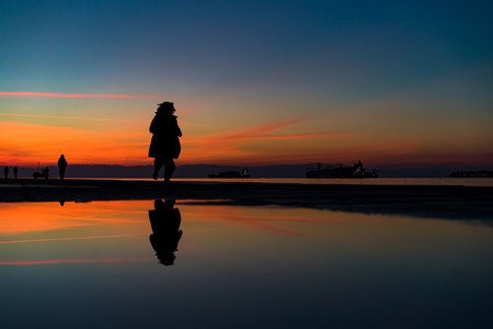 Sihouette of Woman Running by the Sea, against beautiful after sunset color tones