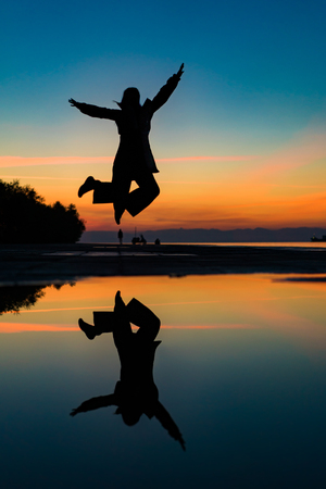 Enjoing Life... Reflection on Water after Rain of  Womans Silhouette Jumping Up by the Sea, against beautiful after sunset color tones