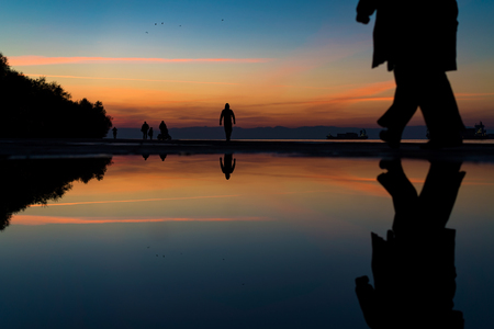 Reflections of People Silhouettes Walking by the Sea, against beautiful after sunset color tones