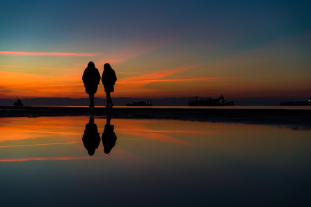Reflections of two Womans Silhouettes Walking by the Sea, against beautiful after sunset color tones