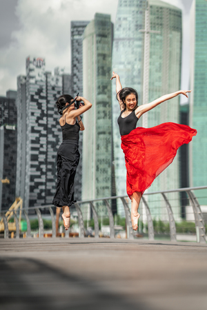 Two beautiful young girls having fun photo shooting on a deck, jumping up, with skyscrapers city background