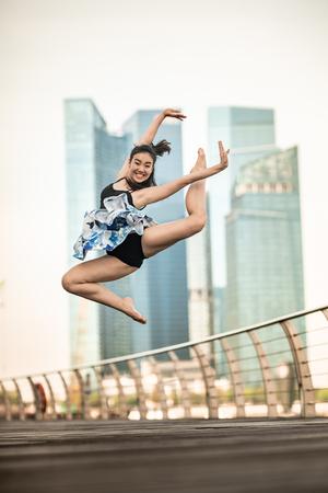 Hermosa joven bailando en la ciudad, con fondo de rascacielos