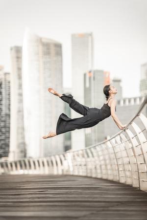 Hermosa joven bailando en la ciudad Foto de archivo
