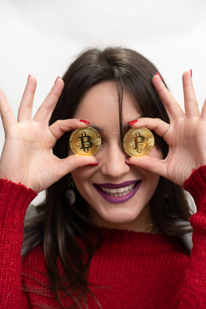 Excited Smiling Successful Woman Holding Bitcoins in front of her eyes