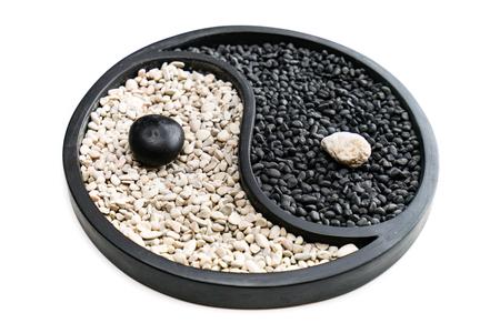 Simbolo Yin e Yang fatto di pietre bianche e nere, isolato su sfondo bianco