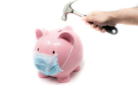 Piggybank wearing surgery mask and hand with hummer ready to crash it. Concept of the impact of a pandemia in world Economy