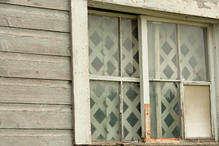 Abandoned wooden barn with broken window and panes