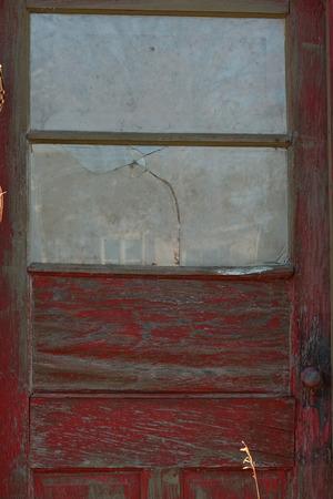 Abandoned building with old red door and broken glass window