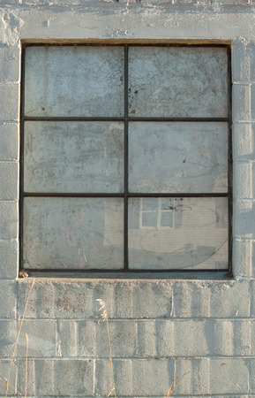 Old abandoned concrete building with window and panes