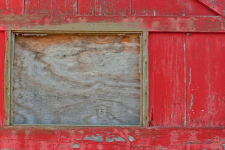 Old door of abandoned industrial building with broken window