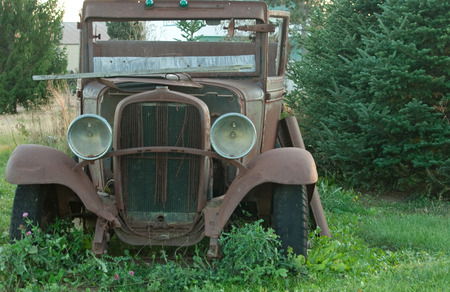 Rusted antique car left as display in field Imagens
