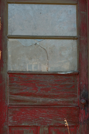 Abandoned building with old red door and broken glass window. Banque d'images