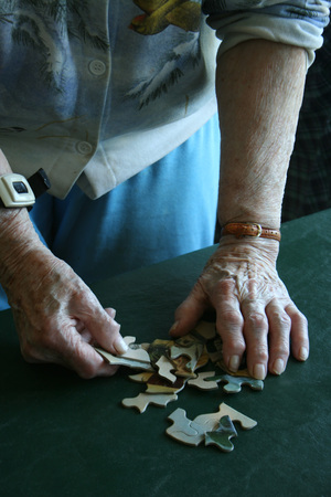 Elderly woman connecting puzzle pieces