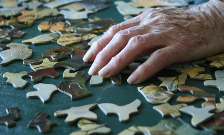 complete solution: Background of elderly senior hand with wrinkles building puzzle Stock Photo