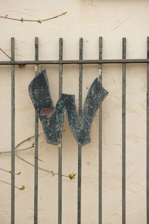 Large Letter W on Gate Against Stucco Wall