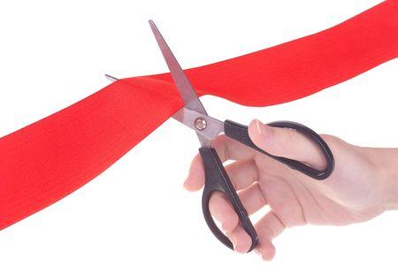 taglio del nastro: Mano con nastro rosso di taglio forbici isolato su sfondo bianco