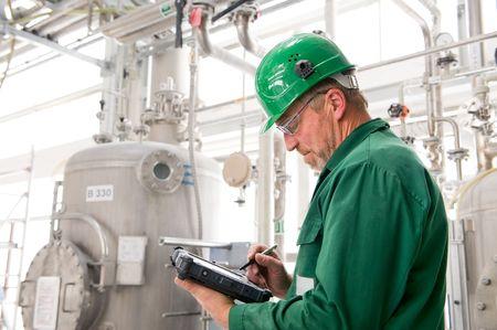 Middelbare leeftijd industriële werknemer met notebook