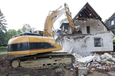Una excavadora de la demolición de casas para la reconstrucción.