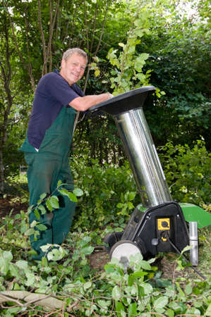 wood cutter: Middle aged forest worker with shredder