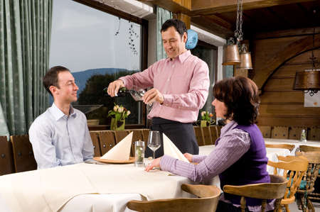 Waiter is serving some wine in a little restaurant  photo
