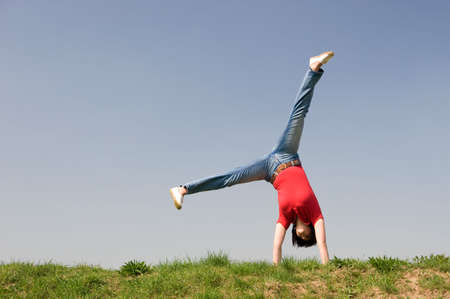 Young woman is turning a cartwheel