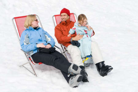 Happy young family with ski boots sitting in chairs photo