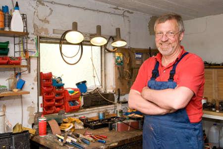 suspender: Smiling and happy senior craftsman in his garage Stock Photo
