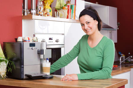 coffee machine: Young and beautiful woman standing in the kitchen beside a coffee machine