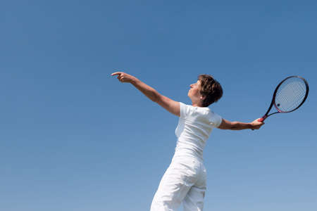 Active senior woman is playing tennis in front of blue sky photo