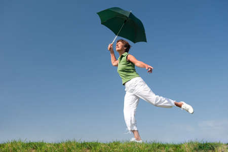 Active senior woman with umbrella is jumping in front of blue sky photo