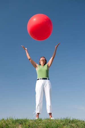 manos levantadas al cielo: Mujer senior activa con una gran bola roja en frente de cielo azul