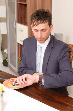 Young businessman with his smartphone looking at the watch photo