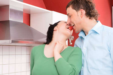 Young and smiling couple together in the kitchen photo