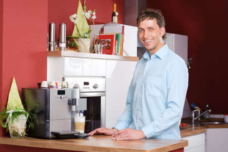 making coffee: Young man standing in the kitchen beside a coffee machine Stock Photo
