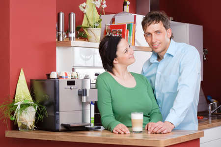 Young couple  standing in the kitchen beside a coffee machine photo