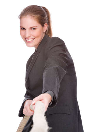 Full isolated studio picture from a young and beautiful business woman doing tug of war photo
