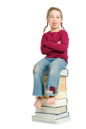 Full isolated studio picture from a young child sitting on some books photo