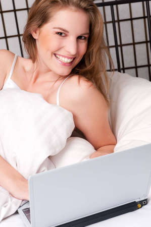 Young woman lies in bed with a notebook photo