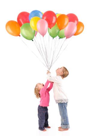 globos de cumplea�os: Foto de estudio aisladas de dos ni�as con globos Foto de archivo
