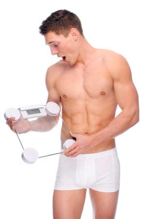 hombre desnudo: Imagen de estudio aislado de un hombre joven desnudo con ropa interior y escalas  Foto de archivo