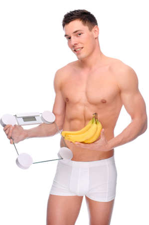 Full isolated studio picture from a young naked man with underwear and scales and banana photo