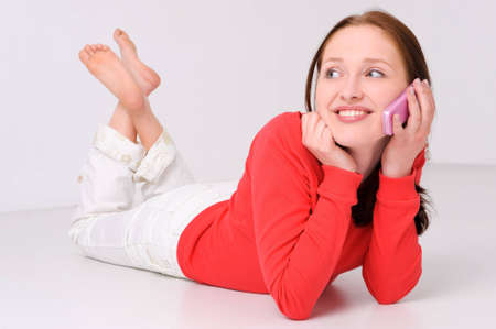 Young woman lying on the floor with cell photo