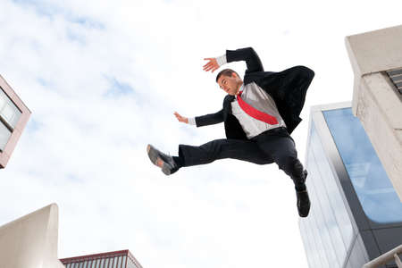 Jumping young buiness man in front of buildings