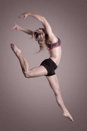 Young and beautiful woman jumping with hands in the air photo