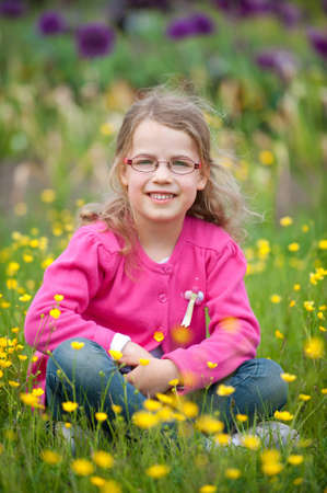 field glass: Smiling young girl sitting in the green Stock Photo