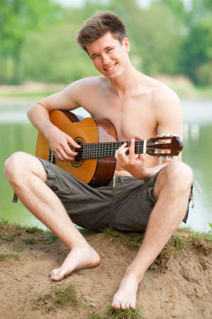 Smiling young man with guitar photo