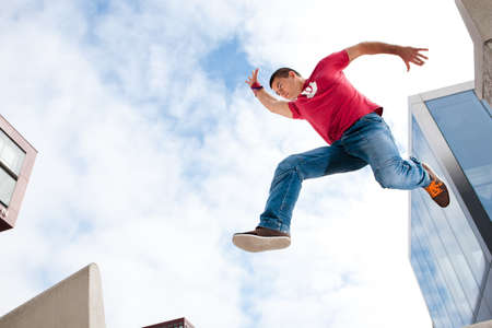Jumping young man in front of buildings