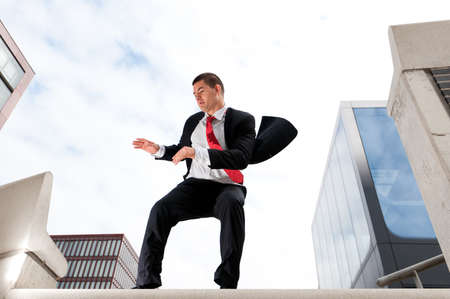 buisinessman: Jumping young buiness man in front of buildings