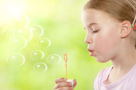 Little girl with soap bubbles in front of green photo