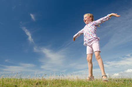 Happy little girl jumping in front of blue sky Stock Photo - 10122211